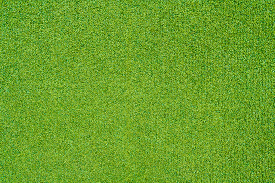 Artificial green grass on the playground as texture, background