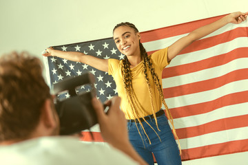 One more shot. Selective focus on a beaming young lady in casual holding a flag of the US while posing for a photo indoors.
