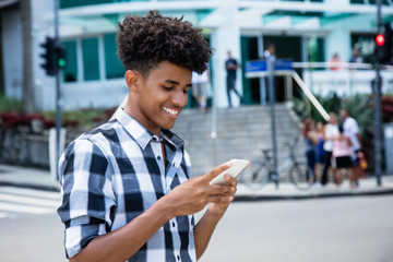 African american young adult sending message with mobile phone