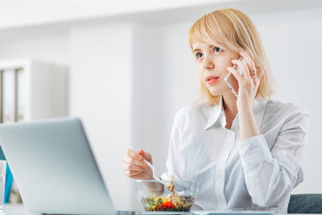 Woman Manager at the Office receiving good news on the phone and eating a salad