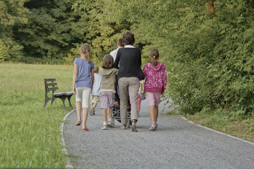 Fototapeta rodzina spaceruje  w parku, kochająca się rodzina na spacerze w parku, odpoczynek na świeżym powietrzu, rodzinne spacery obraz