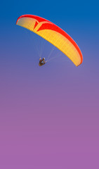 Foto op Aluminium Luchtsport Beautiful yellow and red paraglider flying in colorful sky