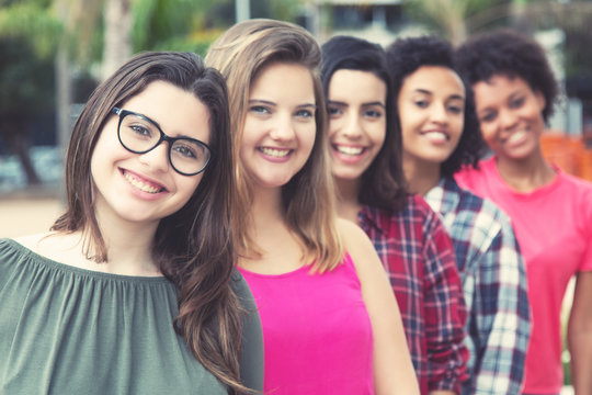 Laughing caucasian young adult woman with  international girls standing in line