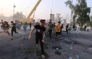 Iraqi protesters run during a protest near the building of the government office in Basra