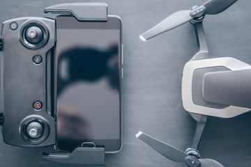 Wall Mural - The concept of using drones in life and industry. Close up Top view Remote and smartphone macro Details. Copy space. Innovation photography concept. Mate color. A new black drone on a black table.