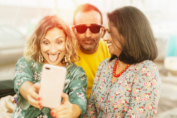 Cheerful friends (two woman and a man) taking selfie with back lighting - Happy youth concept with young people having fun together  - Vintage retro filter