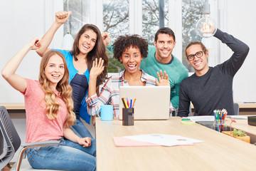 Gruppe jubelnder Studenten mit Laptop