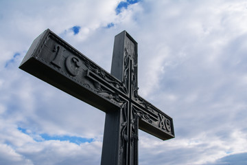 Black cross with symbols against the background of the clear sky, religion, faith