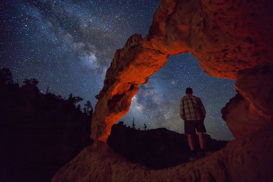 Man under and arch in the Utah desert at night, USA.