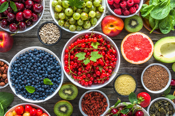 Healthy food selection. Superfoods, fresh organic fruits, assortment of berries, nuts and seeds. Detox antioxidant diet with vegetarian ingredients.