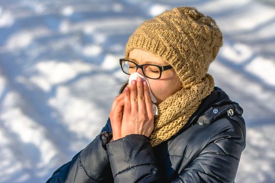 Sneezing woman blowing her nose with a tissue. Concept of people with cold and flu in winter with snow, outdoors.