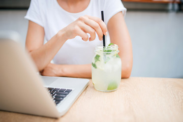 Woman with lemonade and laptop in cafe. Copy space.