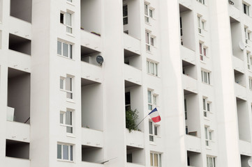 Minimalist architecture. Residential tower with bright light and white color. France flag hanging