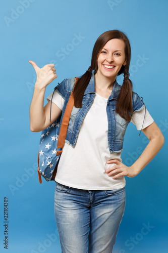 094f89ab5c Portrait of young funny beautiful woman student in denim clothes with backpack  pointing index finger up looking aside isolated on blue background.