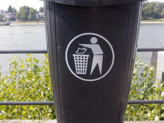 ein grauer Mülleimer ist an einem Geländer befestigt. Im Hintergrund sieht man den Rhein