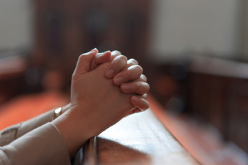 A Christian girl is sitting and praying with broken heart in the church.