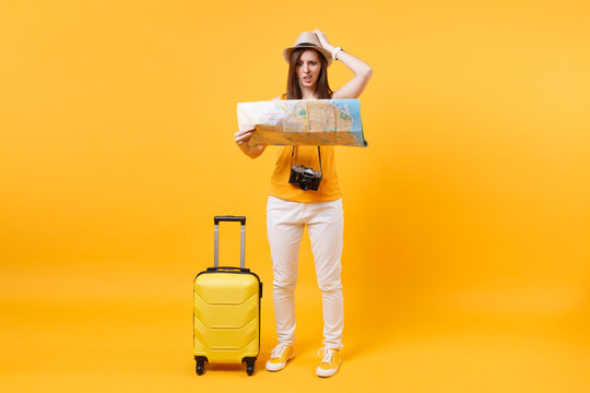 Traveler tourist woman in summer casual clothes, hat with suitcase, city map isolated on yellow orange background. Passenger traveling abroad to travel on weekends getaway. Air flight journey concept.