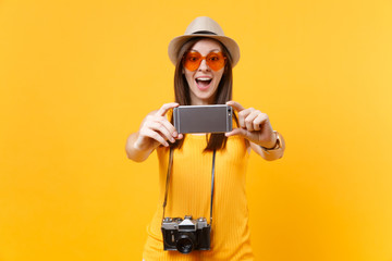 Tourist woman in summer casual clothes, hat doing taking selfie shot on mobile phone isolated on yellow background. Female passenger traveling abroad to travel on weekends getaway. Air flight concept.