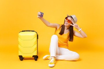 Tourist woman in summer casual clothes, hat doing selfie shot on mobile phone isolated on yellow orange background. Female passenger traveling abroad to travel on weekends getaway. Air flight concept.