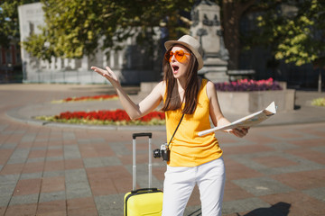 Irritated traveler tourist woman in orange heart glasses with suitcase holding city map spreading hands in city outdoor. Girl traveling abroad to travel on weekend getaway. Tourism journey lifestyle.