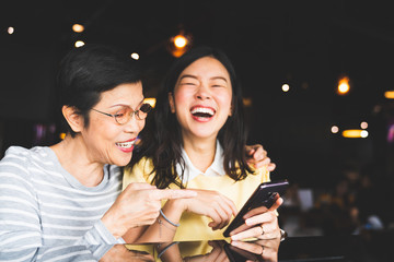 Asian mother and daughter laughing and smiling on a selfie or photo album, using smartphone together at restaurant or cafe, with copy space. Family love, holiday activity, or modern lifestyle concept Fotoväggar