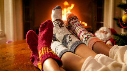 Family wearing warm knitted socks relaxing at house with burning fireplace