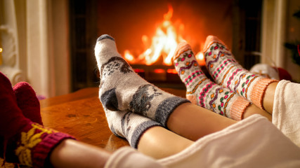 Closeup image of feet in warm woolen socks and burning fireplace at house