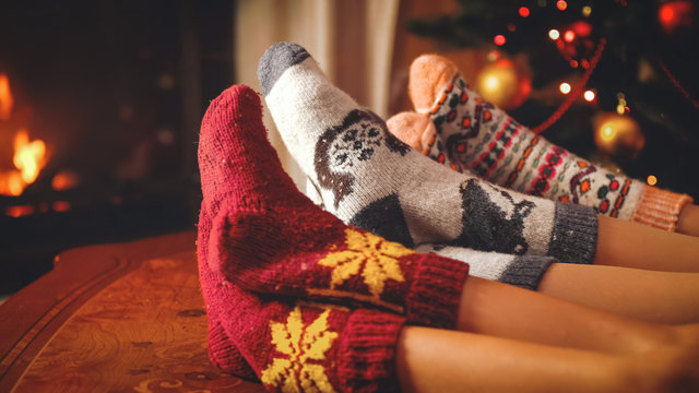 Toned photo of family in woolen socks lying next to burning fireplace at living room