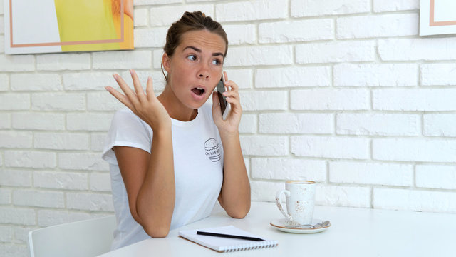 Surprised woman during speaking on the cell phone