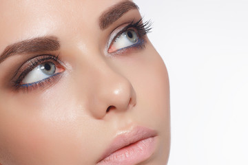 Close-up of female eyes with trendy evening make-up, thick even eyebrows and long rustnitsami. Gray-blue eyes, lenses, eyesight, cosmetology, make-up