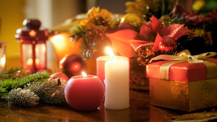 Closeup image of burning candles and gifts in boxes on table decorated for Christmas