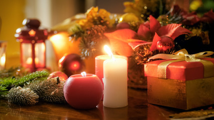 Closeup image of red and white candle on wooden table decorated for Christmas