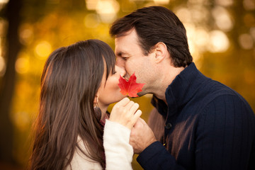 Romantic Couple Kissing Behind Red Autumn Leaf