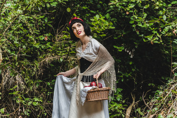 Snow White is entering the forest with a basket full of apples. She seems amazed. Fotomurales