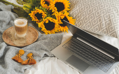 Cup with hot cappuccino, gray pastel woolen blanket, sunflowers, bedroom, morning concept