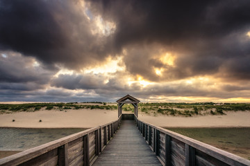 Architecture and art along the Dutch coast with beautiful sunset and threatening clouds along the beach and the dunes