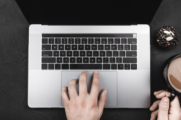 Hands of a laptop user who drinks their coffee at breakfast, top view