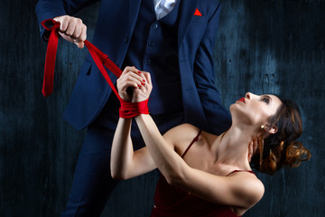 Couple in dating. Rich man male dress skirt tying woman hands. Woman female in expensive red evening dress with tied hands by red tie on dark background. Henpecked violence issue relationship concept.