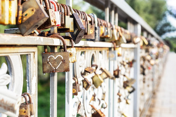 Red heart padlock locked on fence. Lock in shape of heart as symbol of eternal love