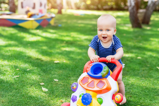 Cute little boy learning to walk with walker toy on green grass lawn at backyard. Baby laughing and having fun making first step at park on bright sunny day outdoors. Happy childhood concept