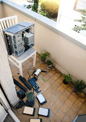Home balcony with vacuum pump to clean computer workstation case on balcony