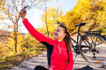 Young and active woman make selfie photo near bicycle