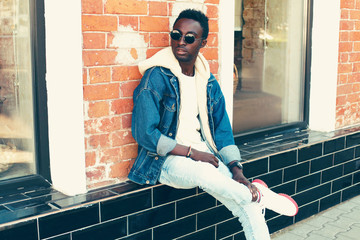 Wall Mural - Fashion african man wearing jeans jacket with hood poses on city street