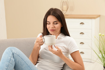 Beautiful woman with cup sitting on sofa at home