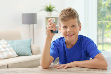 Little boy with asthma inhaler at table indoors