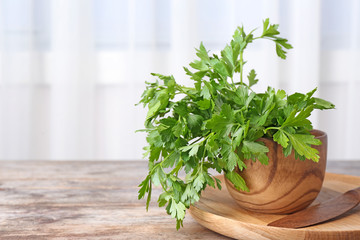 Bowl with fresh green parsley on table. Space for text