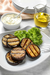 Plate with fried eggplant slices on table