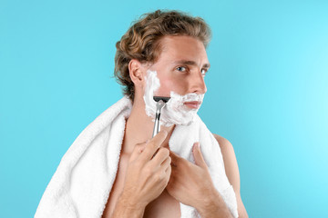 Handsome young man shaving on color background