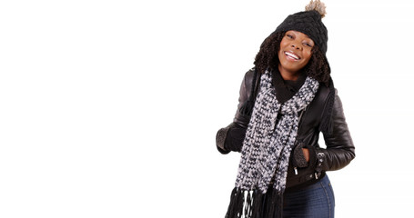 Cute black woman in winter clothes turns around to smile at camera on white