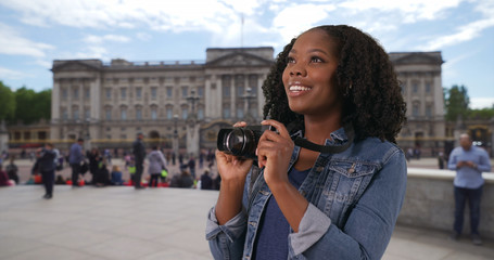Portrait of excited tourist taking photos with camera outside Buckingham Palace